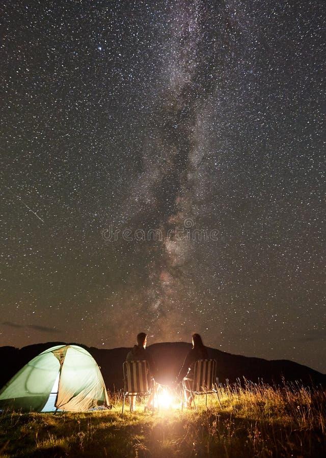 Junte a los turistas en el campo de la noche en monta?as debajo del cielo estrellado fotos de archivo