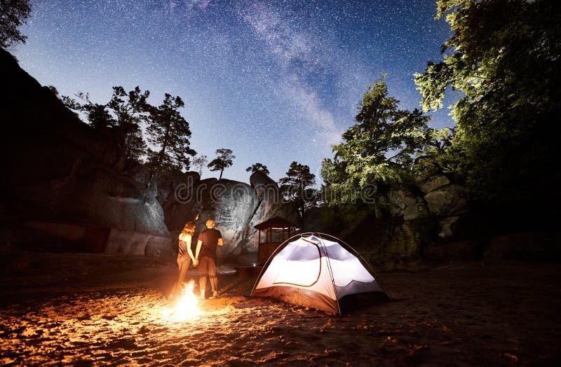 Junte a los turistas que descansan al lado del campo, tienda de la hoguera en la noche foto de archivo libre de regalías