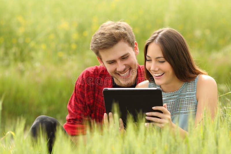 Junte los vídeos de observación en una tableta en un campo imagenes de archivo