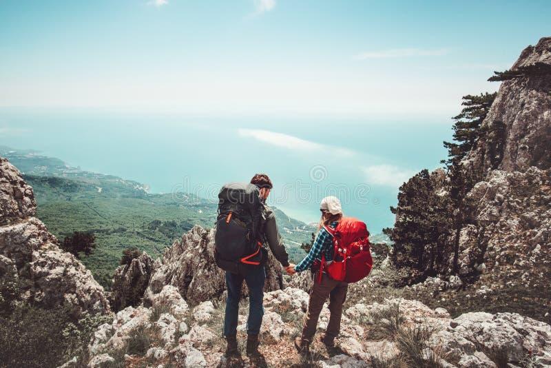 Junte a los viajeros hombre y mujer que llevan a cabo las manos que disfrutan de la opinión aérea de las montañas fotos de archivo libres de regalías