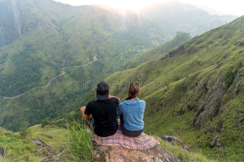 Junte a los viajeros hombre y mujer que se sientan en el acantilado, relajándose Opinión aérea de las montañas imagen de archivo