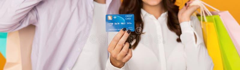 Junte mostrar la tarjeta de crédito que sostiene bolsos de compras imagenes de archivo