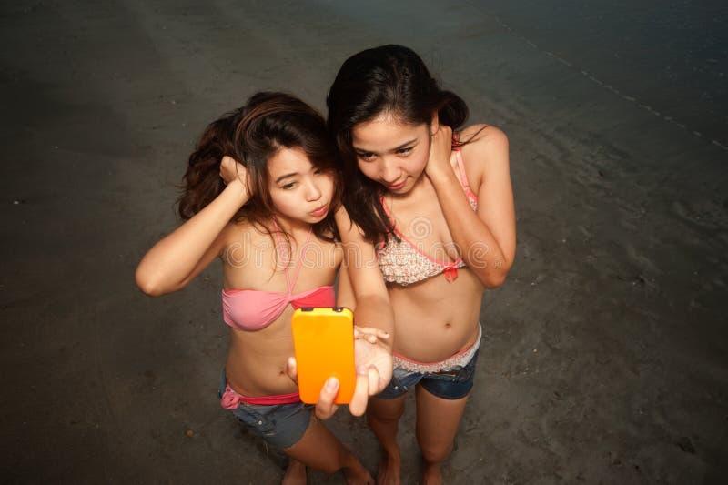 Junte a mulher consideravelmente tailandesa alegre com o telemóvel na praia. fotos de stock royalty free