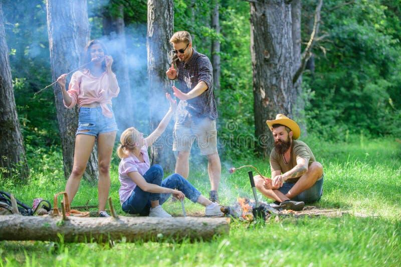 Junte-se ao piquenique do verão Os amigos que encontram-se perto da fogueira para pendurar para fora e preparar-se roasted o fund foto de stock