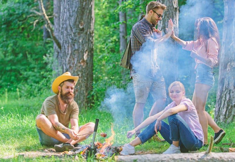 Junte-se ao piquenique do ver?o Os amigos que encontram-se perto da fogueira para pendurar para fora e preparar-se roasted o fund fotos de stock royalty free