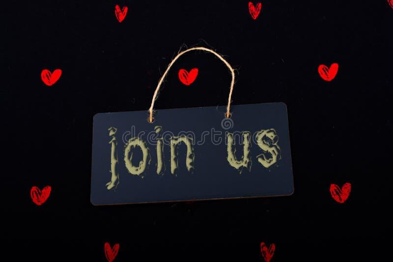Junte-se nos etiqueta em um quadro de mensagens preto e em uns corações vermelhos fotografia de stock