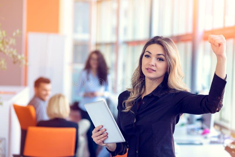 Junte-se a uma era digital Jovem mulher alegre que guarda a tabuleta digital quando seus amigos que trabalham no fundo imagens de stock royalty free