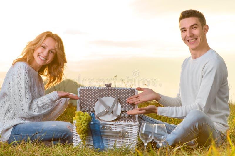 Junte sentar y la presentación de la comida campestre blanca de la cesta en una hierba fotos de archivo
