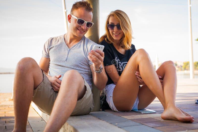 Junte sentarse cerca del mar y la mirada en el teléfono y la sonrisa fotografía de archivo