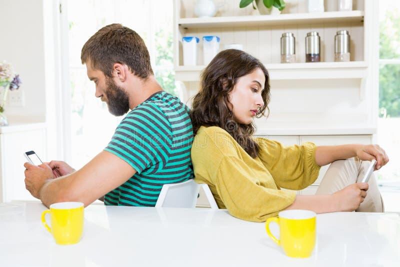 Junte sentarse de nuevo a la parte posterior y al texto que ensucian en el teléfono móvil imagen de archivo libre de regalías