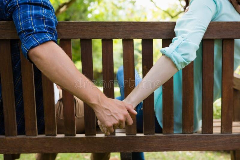 Junte sentarse en banco y llevar a cabo la mano en jardín imagenes de archivo