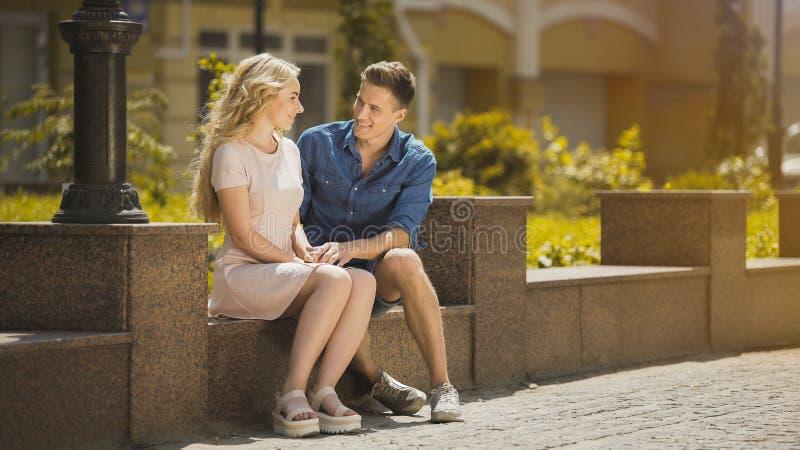 Junte sentarse en el banco, individuo que admira a la muchacha rubia en la primera fecha, humor romántico fotos de archivo libres de regalías