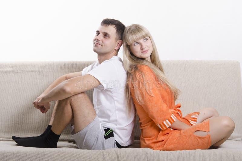Junte sentarse en el sofá con el suyo de nuevo a uno a y la mirada en el marco fotos de archivo