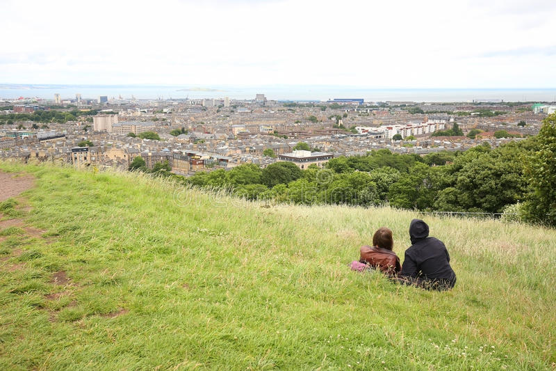 Junte sentarse en la colina de Calton y disfrutar de las vistas asombrosas de Edimburgo, Escocia foto de archivo