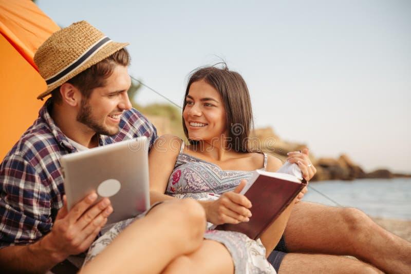 Junte sentarse en la tienda usando la tableta y el libro de lectura fotos de archivo libres de regalías