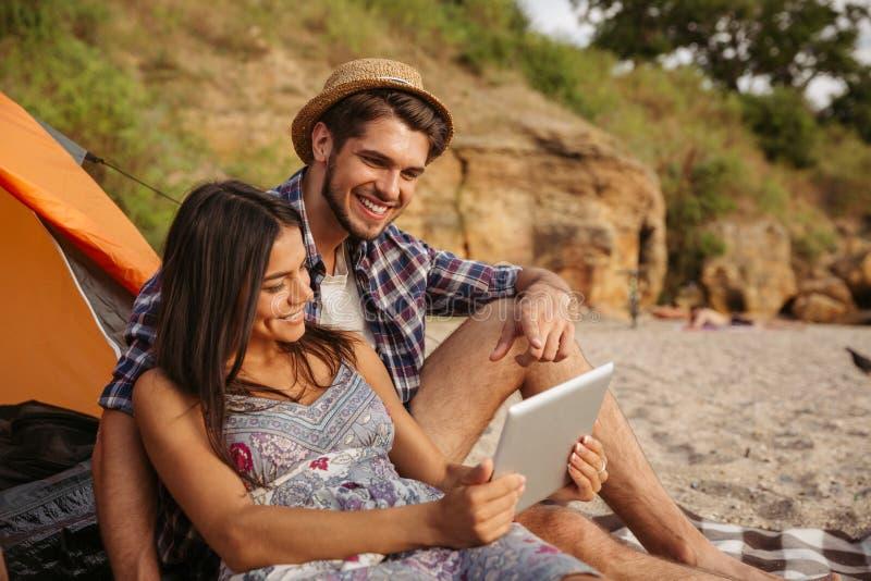 Junte sentarse en la tienda y usar la tableta imagenes de archivo