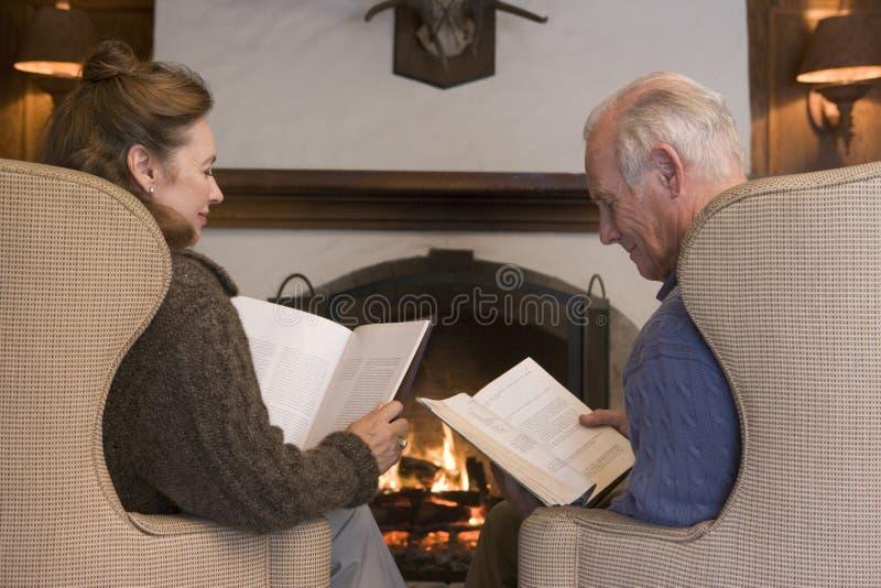 Junte sentarse en sala de estar por la lectura de la chimenea fotos de archivo libres de regalías