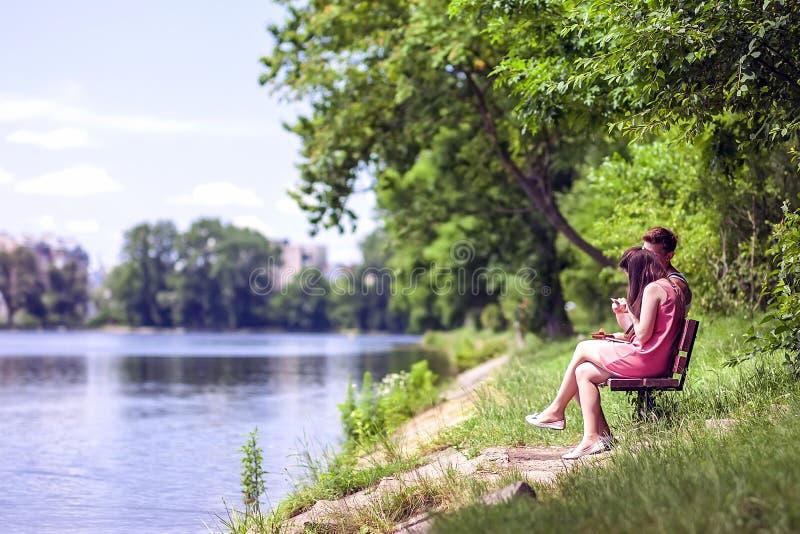 Junte sentarse en un banco al lado de un lago en un día de verano soleado imagen de archivo libre de regalías