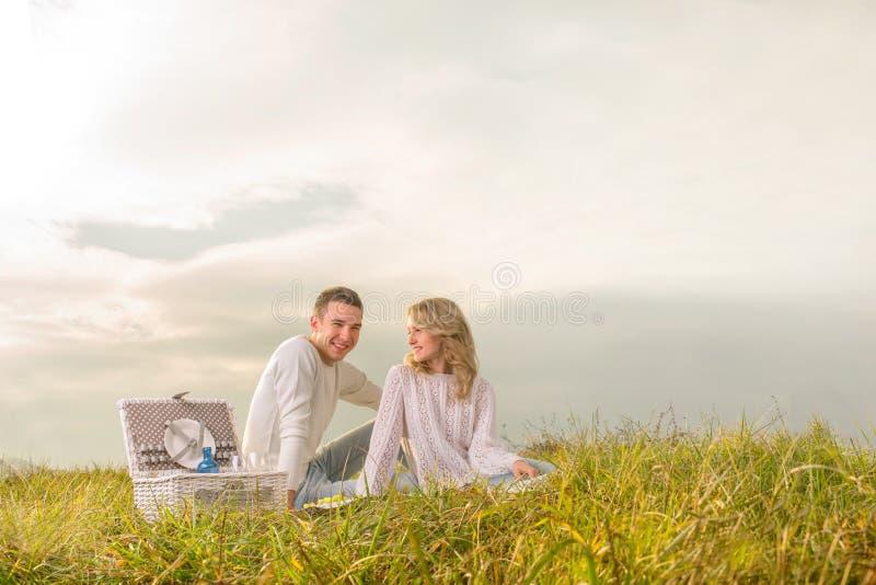 Junte sentarse en una comida campestre con la cesta blanca debajo del cielo fotos de archivo