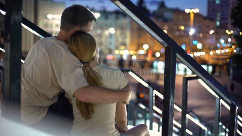 Junte sentarse y el abrazo en las escaleras, disfrutando de la opinión hermosa de la ciudad, romántica foto de archivo
