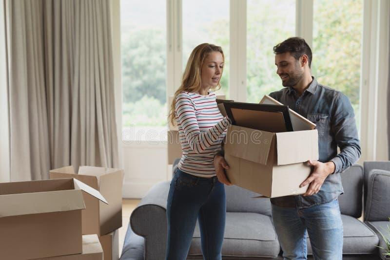 Junte sostener la caja de cartón en nuevo hogar imagenes de archivo