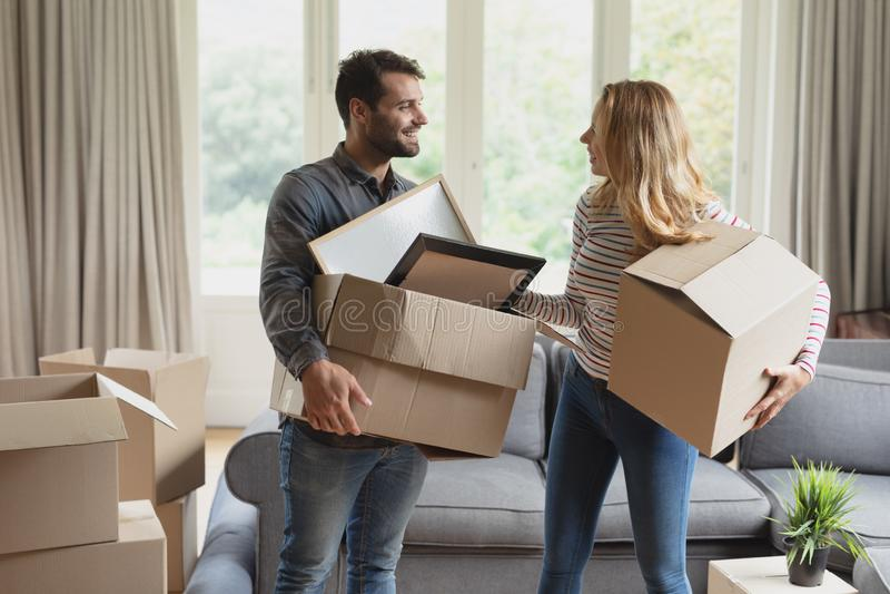 Junte sostener la caja de cartón en nuevo hogar imágenes de archivo libres de regalías