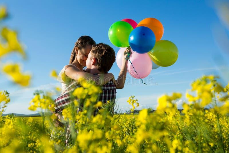 Junte sostener los globos coloridos y el abarcamiento en campo de la mostaza fotos de archivo libres de regalías