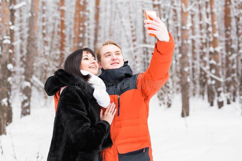 Junte tomar el autorretrato con el teléfono elegante en parque del invierno Selfie joven hermoso de los pares imágenes de archivo libres de regalías