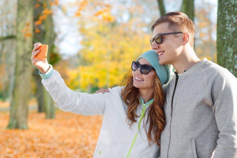 Junte tomar el selfie por smartphone en parque del oto?o imagen de archivo