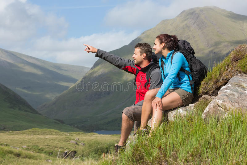 Junte tomar una rotura después de caminar cuesta arriba con señalar del hombre foto de archivo