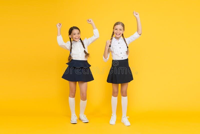 Junto nós somos vencedores Pouco alunos que fazem gestos do vencedor no fundo amarelo Vencedores pequenos bonitos que apreciam fotos de stock royalty free