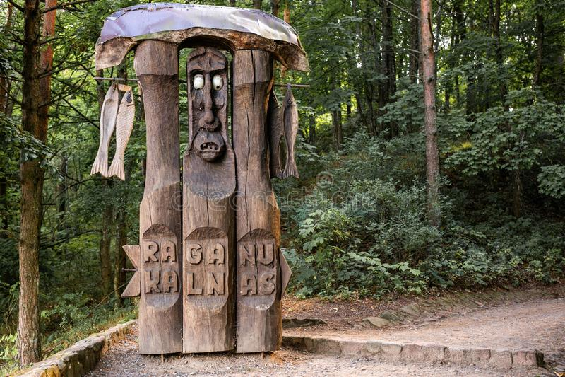 JUODKRANTE, LITOUWEN - AUGUSTUS, 2018: Traditionele Litouwse Raganu-de kunstbeeldhouwwerken van het kalnashoutsnijwerk van volksm stock fotografie