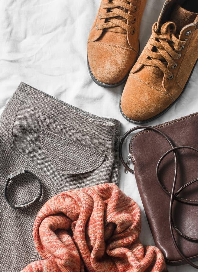 Jupe réglée d'habillement du ` s de femmes, bottes de suède, écharpe, sac mortuaire croisé en cuir, fond clair, vue supérieure photographie stock
