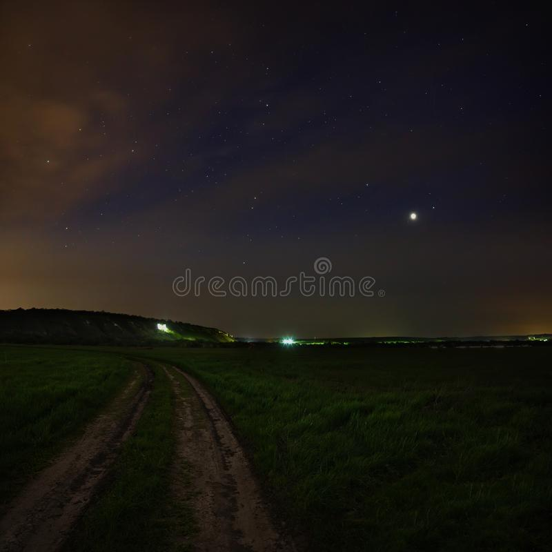 Jupiter in the night sky with the stars. Rural road at dusk. royalty free stock photography