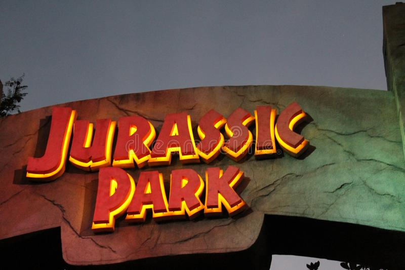 Jurassic Park ride sign in the evening. Jurassic Park ride sign illuminated backlit in the evening at Universal Studios park in Orlando, Florida stock image