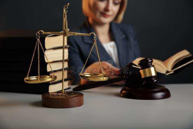 Juridical concept. Closeup picture of reading woman. Gavel and scale on the table. Juridical concept. Closeup picture of reading woman. Gavel and scale on the stock photography