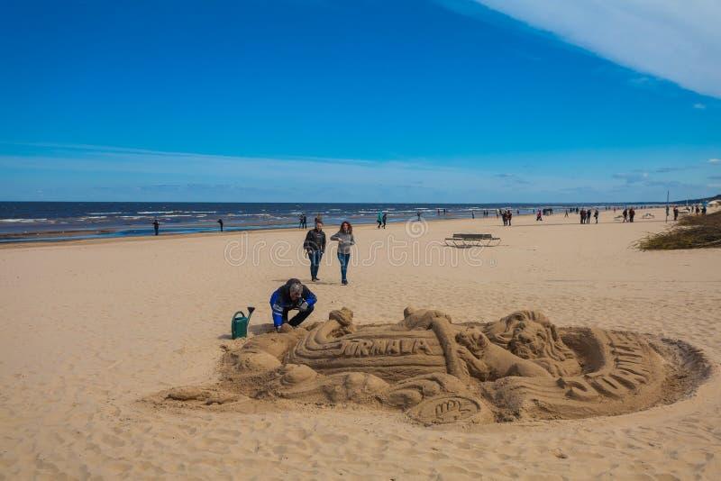Jurmala,拉脱维亚- 2017年5月7日:人雕刻从沙子的图,并且人们在t的沙滩走 免版税库存照片