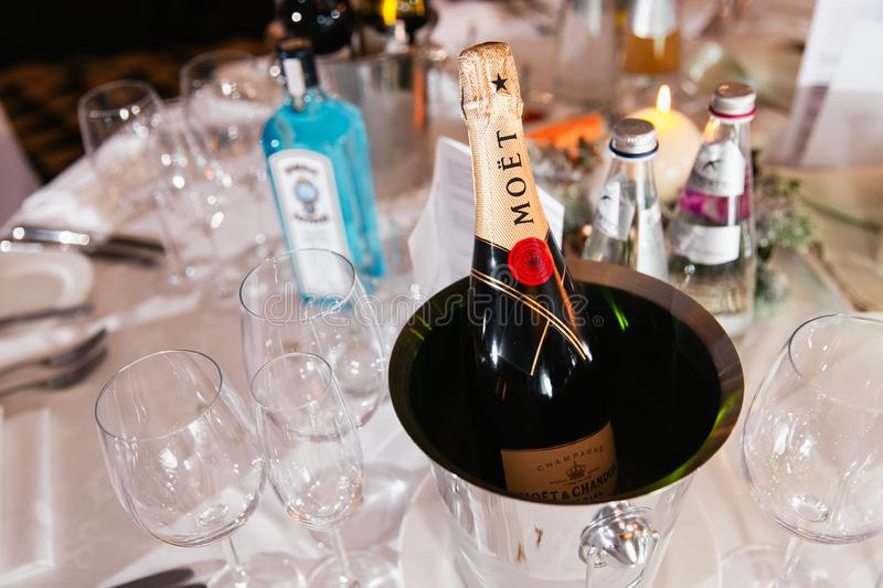 JURMALA, LATVIA - JANUARY 01, 2019: Moet luxury champagne on a table with a bottle of gin Bombay in the background royalty free stock photography