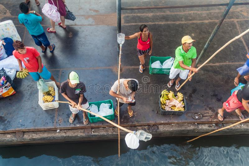 JURUTI, BRAZIL - JUNE 28, 2015: Sellers use a long stick to deliver the goods to passengers of a river boat which is stock photo