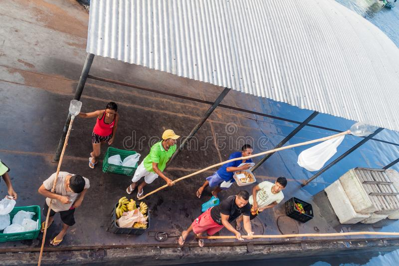 JURUTI, BRAZIL - JUNE 28, 2015: Sellers use a long stick to deliver the goods to passengers of a river boat which is stock image