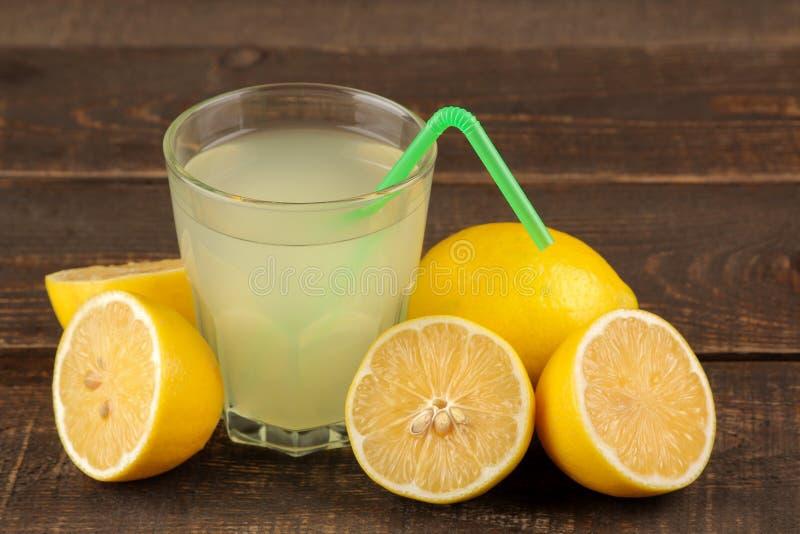 Jus d'agrumes jus de citron dans un verre avec les citrons frais sur une table en bois brune photo stock