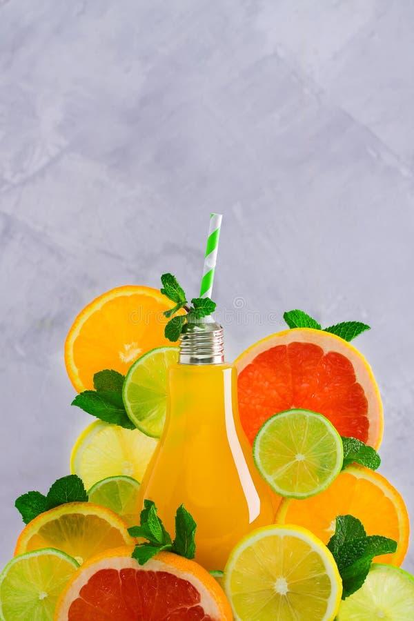 Jus d'agrumes de fruit dans les tranches en forme de lampe en verre et de fruits frais image libre de droits