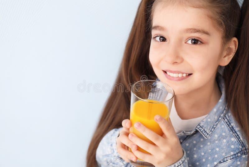 Jus d'agrumes potable drôle de petite fille sur le fond de couleur image libre de droits