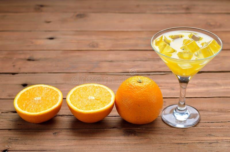 Jus d'orange avec de la glace dans un verre de martini sur une table en bois photo libre de droits