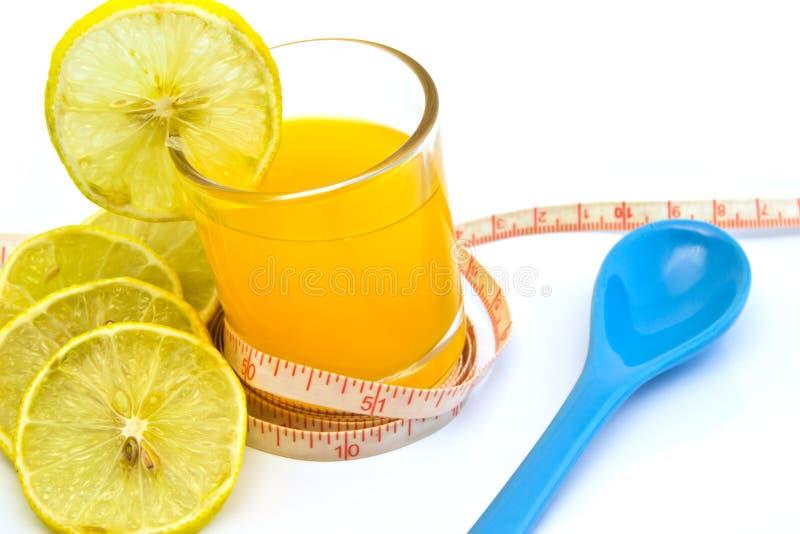 Jus d'orange avec la bande et la cuillère de mesure, d'isolement sur le blanc photo stock