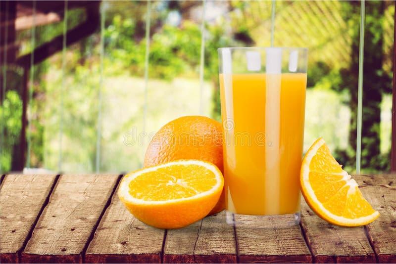 Jus d'orange avec le fruit frais sur la table dans le jardin photo stock