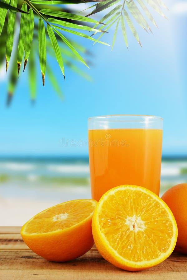 Jus d'orange avec les oranges et le fond de plage de tache floue photos stock