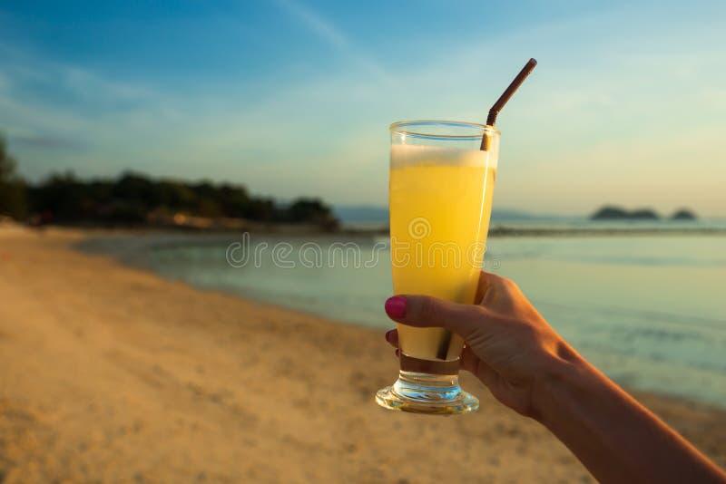 Jus d'orange chez des mains de la femme sur la plage avec le fond de mer photo stock