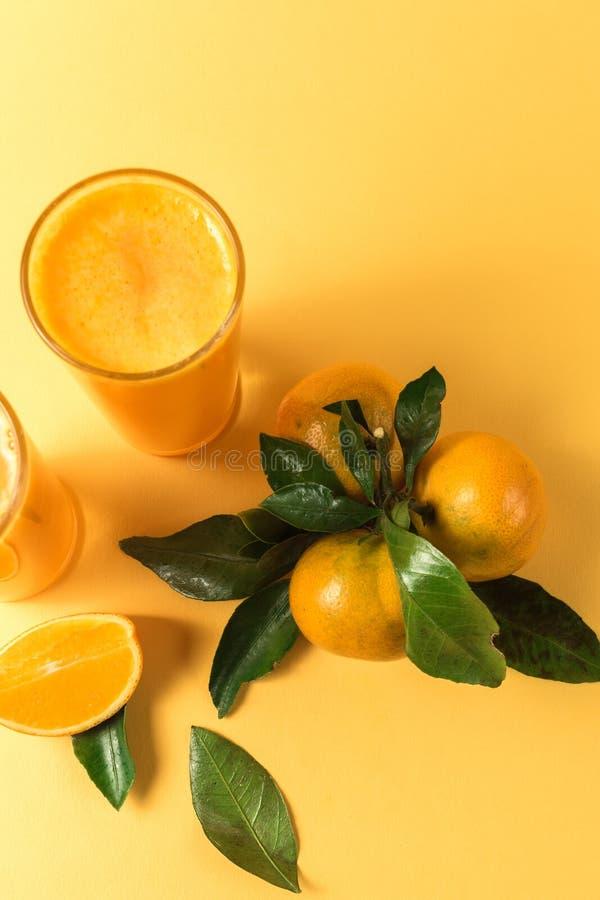 Jus d'orange dans un fruit en verre et mûr de mandarine avec les feuilles vertes, au-dessus du fond jaune photographie stock