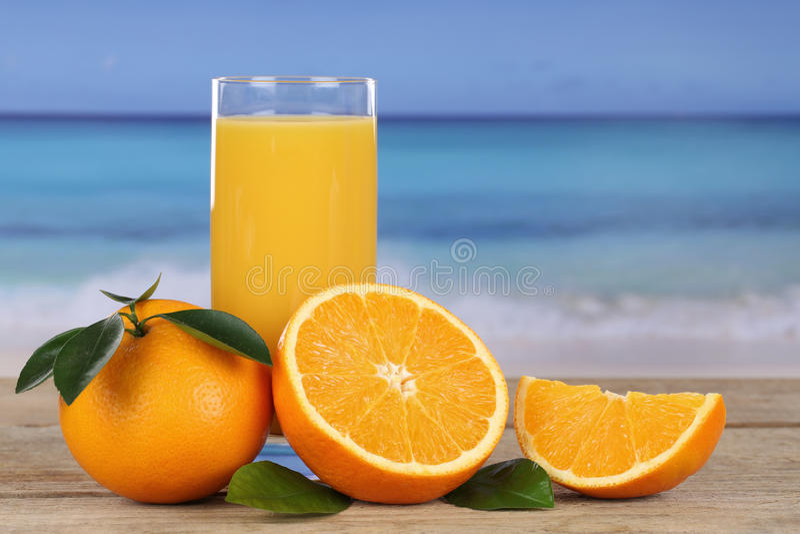 Jus d'orange en sinaasappelen op het strand stock foto